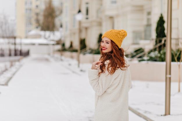 Vrolijke gembervrouw die terugkijkt tijdens een wandeling door de winterstad. bevallig europees meisje dat in sneeuwochtend koelen.