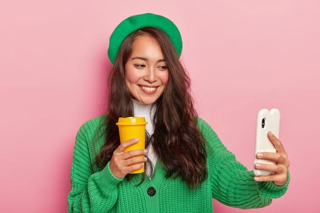 Vrolijke gemengd ras dame in groene baret en gebreide trui, maakt selfie portret met mobiele telefoon, vormt met koffiekopje