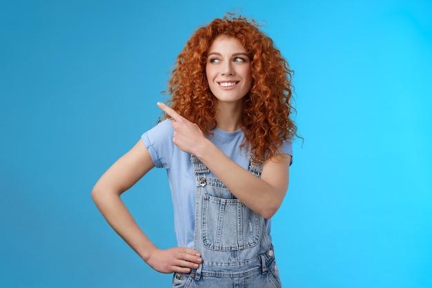 Vrolijke gemotiveerde charismatische knappe gelukkig lachende roodharige 25s krullend-haired vrouw zomer tuinbroek wijzend linker bovenhoek opzij kijken blij show promo suggereren try-out. ruimte kopiëren