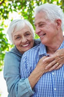 Vrolijke gepensioneerd echtpaar knuffelen