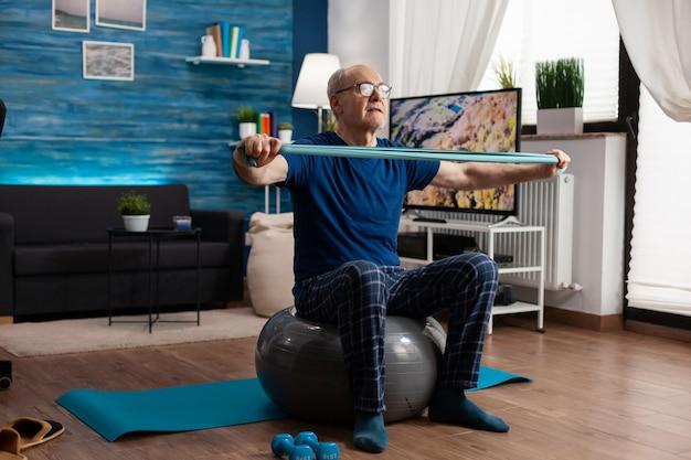 Vrolijke gepensioneerde senior man die armspieren oefent met behulp van elastische weerstandsband