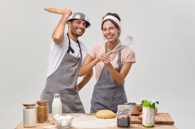 Vrolijke getrouwde vrouw en man hebben kookles, vechten met keukenbenodigdheden, genieten van favoriete hobby thuis, nemen deel aan een culinaire show, maken deeg om heerlijk eten te bakken of pannenkoeken te maken.