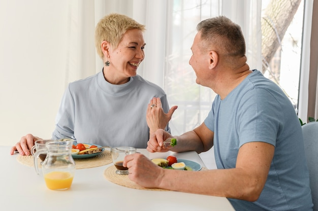 Vrolijke gezonde senior paar eten ontbijt samen glimlachend en lachen