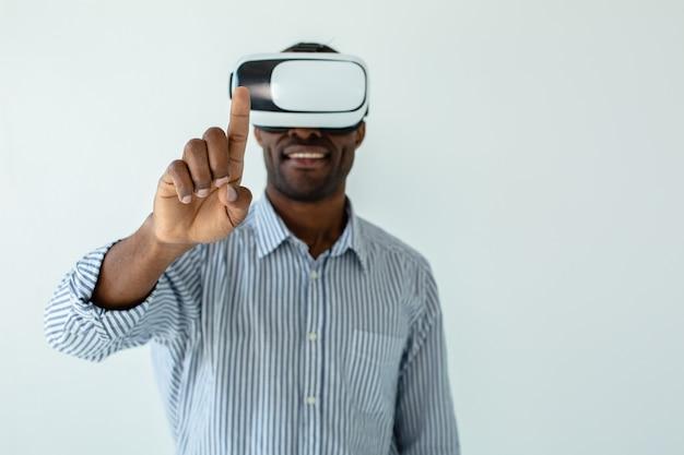 Vrolijke glimlachende afro-amerikaanse man met een vr-bril terwijl hij je aanraakt