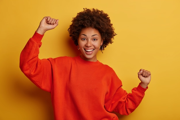 Vrolijke glimlachende afro-amerikaanse vrouw heeft plezier, spreekt geluk uit, balde vuisten, geniet van een feestje met vrienden