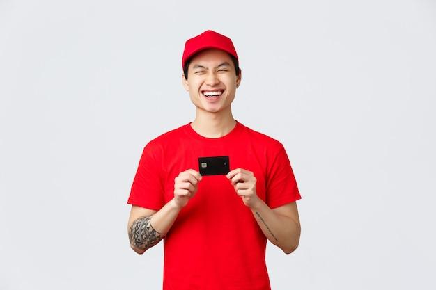 Vrolijke glimlachende aziatische bezorger in rode pet en t-shirt uniform, lachend als bevordering van gemakkelijke betaling voor online bestellingen terwijl in quarantaine van het coronavirus thuis blijven, koerier houdt creditcard vast