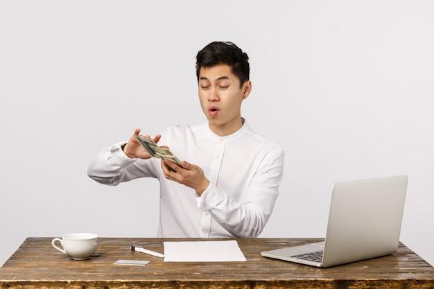Vrolijke glimlachende aziatische jonge ondernemer die bankbiljetten werpen op het kantoor