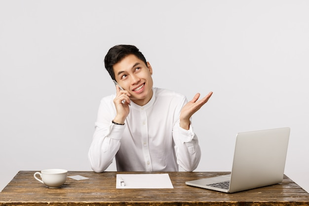 Vrolijke glimlachende aziatische jonge ondernemer die bij de telefoon op het kantoor spreken