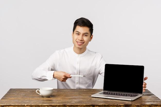 Vrolijke glimlachende aziatische jonge ondernemer die laptop richten op het kantoor