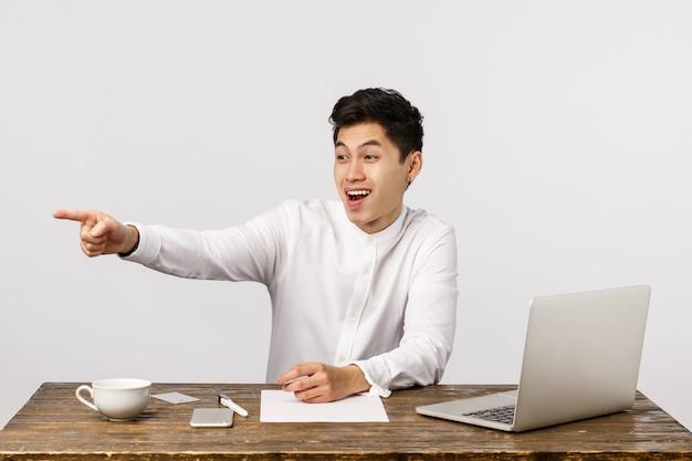 Vrolijke glimlachende aziatische jonge ondernemer die op het kantoor lachen