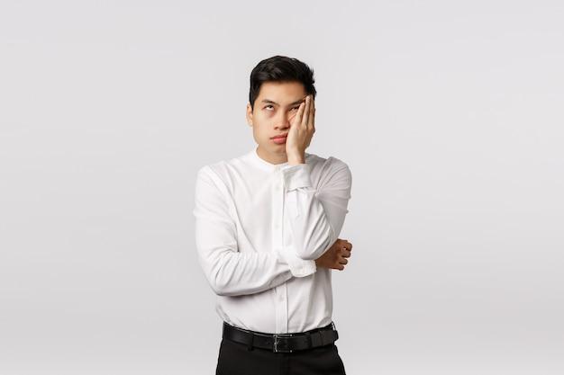 Vrolijke glimlachende aziatische jonge ondernemer met wit overhemd die met hand op gezicht wordt geïrriteerd