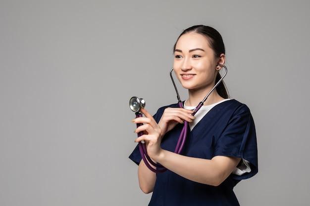 Vrolijke glimlachende aziatische vrouwelijke arts die met een stethoscoop onderzoekt, geïsoleerd over een witte muur