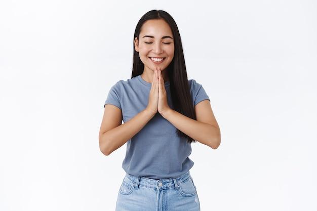 Vrolijke, glimlachende gelukkige aziatische vrouw die wens doet in de buurt van heiligdom, ogen dicht en grijnzend terwijl ze droomt over iets geweldigs, hand in hand bidden, smeken, witte muur hoopvol staan