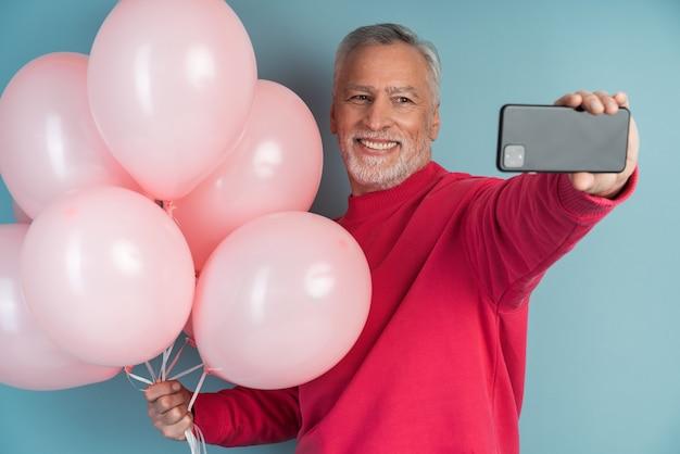 Vrolijke, glimlachende, grijsharige man met ballen op een blauwe muur