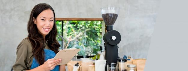 Vrolijke glimlachende jonge aziatische vrouwenondernemer bij koffiewinkel tegen