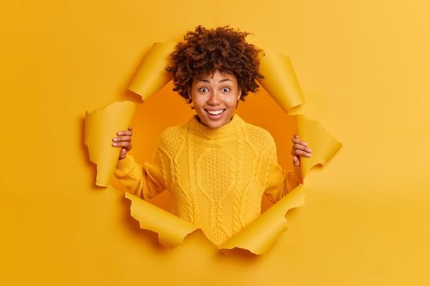 Vrolijke glimlachende jonge donkere afro-amerikaanse vrouw vormt in gescheurd papier