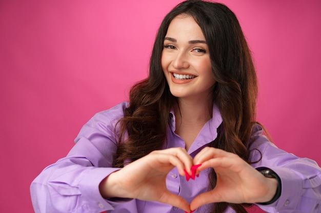 Vrolijke glimlachende jonge vrouw die hartteken toont tegen roze achtergrond
