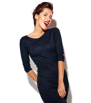 Vrolijke glimlachende knipogende mode vrouw gek in casual zwarte kleding met rode lippen op witte muur