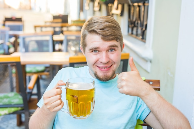 Vrolijke glimlachende man die een grote bierpul vasthoudt en zijn duimen buiten laat zien