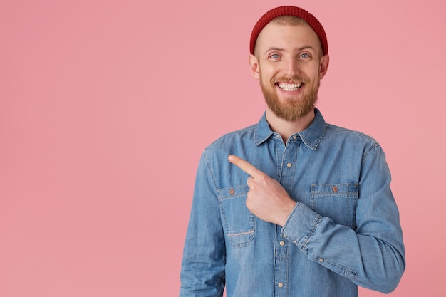 Vrolijke glimlachende man met blauwe ogen in rode hoed met rode dikke baard voelt geluk met witte gezonde tanden, in spijkerblouse, geïsoleerd op roze muur wijst met wijsvinger naar links op kopie ruimte