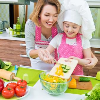 Vrolijke glimlachende moeder en dochter die een salade koken in de keuken.