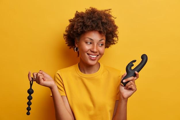Vrolijke glimlachende vrouw blij om terug te komen uit sekswinkel, houdt anale kralen vast voor stimulatie door beweging in de anus, vibrator om climax te bereiken, in goed humeur, kan niet wachten tot masturbatie
