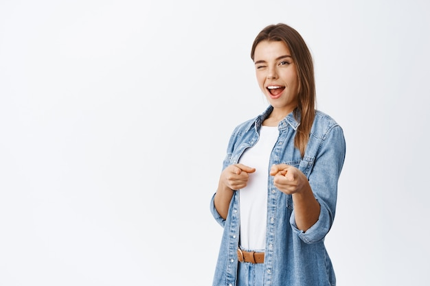 Vrolijke glimlachende vrouw die uitnodigt of rekruteert, met de vingers naar voren wijst en knipoogt om iemand te prijzen, in een casual outfit tegen de witte muur staat