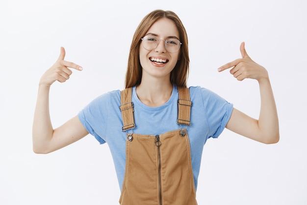 Vrolijke glimlachende vrouw in glazen wijzend op zichzelf of logo