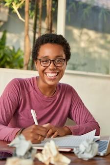 Vrolijke glimlachende zwarte student werkt op cursuspapier