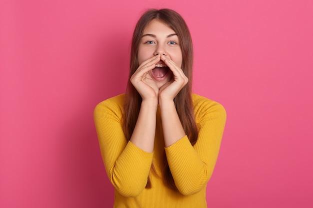 Vrolijke grappige jonge vrouw, gekleed in gele trui schreeuwen met handgebaar in de buurt van mond geïsoleerd over roze muur, dame met lang haar