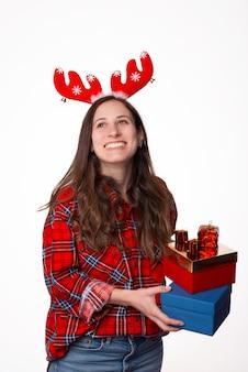Vrolijke grappige jonge vrouw in geruit overhemd met rode hertengeweien houdt een kerstcadeaus en lachen