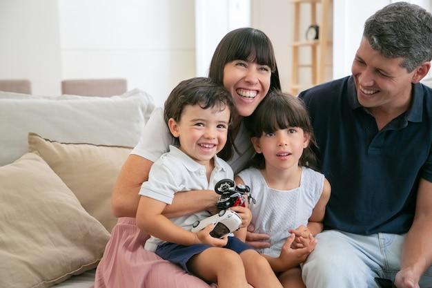 Vrolijke grappige ouders en twee kinderen kijken naar grappige film thuis, zittend op de bank in de woonkamer en wegkijken en lachen.