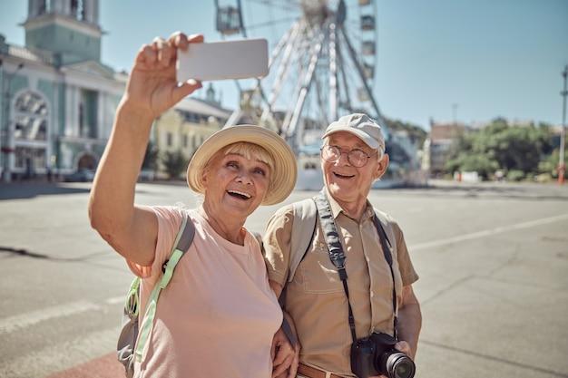 Vrolijke grijsharige dame die zichzelf en haar echtgenoot fotografeert tegen het reuzenrad in het stadscentrum
