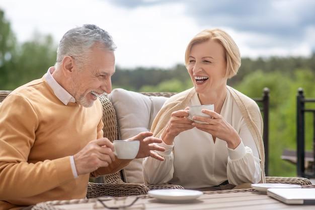 Vrolijke grijsharige man en zijn opgewekte, knappe vrouwelijke echtgenoot genieten van elkaars gezelschap bij het ontbijt