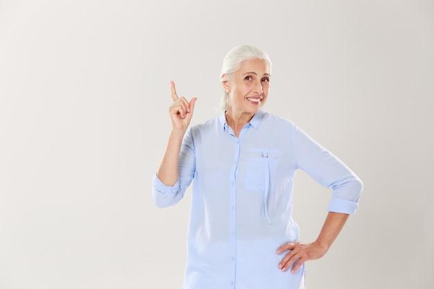 Vrolijke grijze oude dame in blauw shirt, wijzend met de vinger naar boven