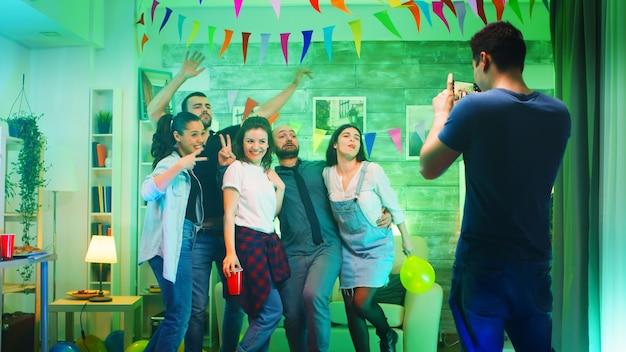 Vrolijke groep mensen die lacht op het feest terwijl de jonge man foto's van hen maakt.