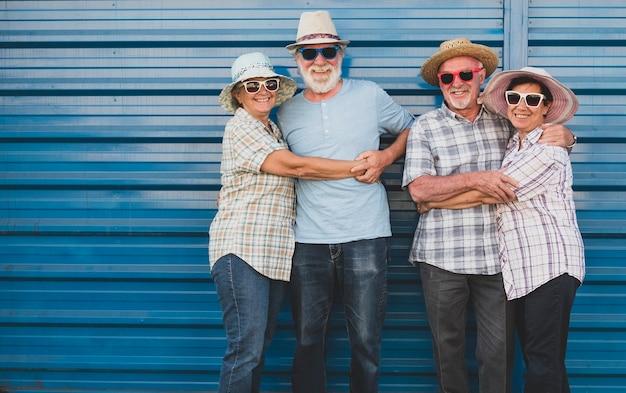 Vrolijke groep van vier mensen met gekleurde zonnebrillen knuffelen elkaar glimlachend en kijkend naar de camera