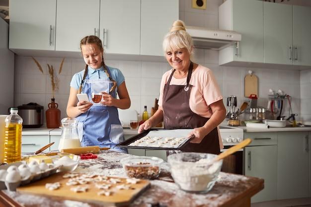 Vrolijke grootmoeder die deeg klaarmaakt om in de oven te gaan