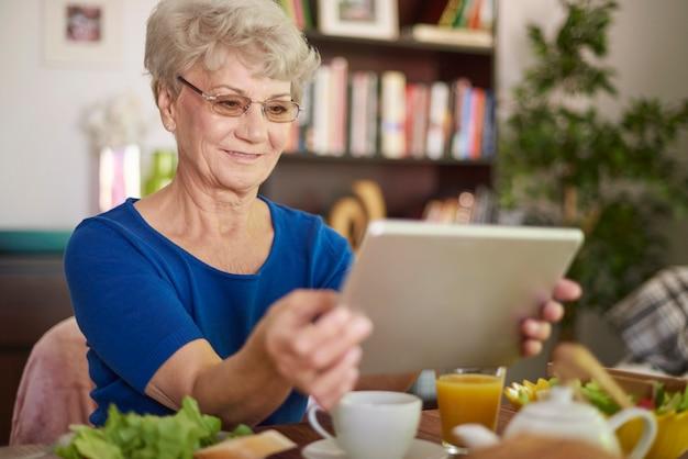 Vrolijke grootmoeder met haar digitale tablet