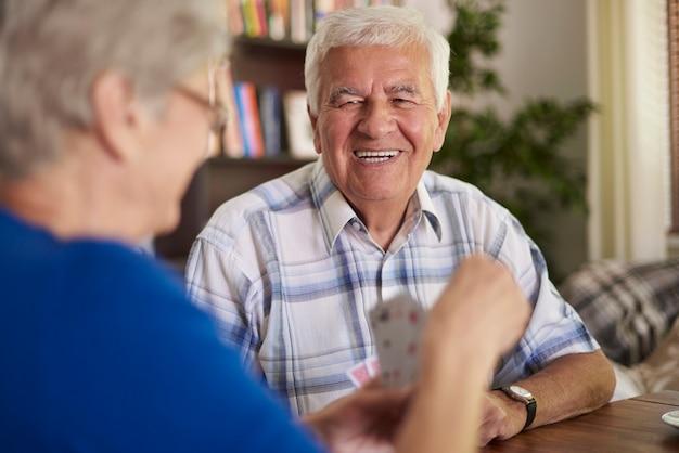 Vrolijke grootouders speelkaarten in de middag