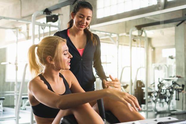 Vrolijke gymnastiekinstructeur die met cliënten spreekt en advies over materiaal geeft.