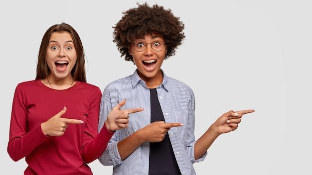 Vrolijke halfbloedmeisjes hebben een grappige, vreugdevolle gezichtsuitdrukking, staan dicht bij elkaar, duiden met beide wijsvingers opzij op blanco kopie ruimte om een prachtige plek te adverteren. multiculturele verkopers
