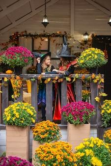 Vrolijke halloween-meisjes in heksenkostuums hebben plezier in de herfst in de buurt van het huis