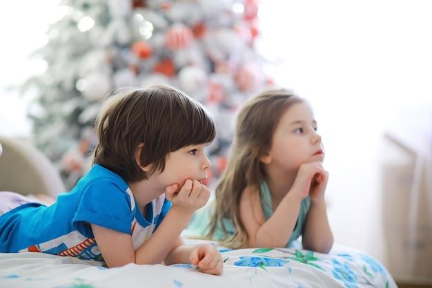 Vrolijke heldere kerst. mooie baby geniet van kerstmis. jeugdherinneringen. santa meisje klein kind vieren kerst thuis. vakantie met het gezin. meisje schattig kind vrolijke stemming spelen in de buurt van kerstboom.