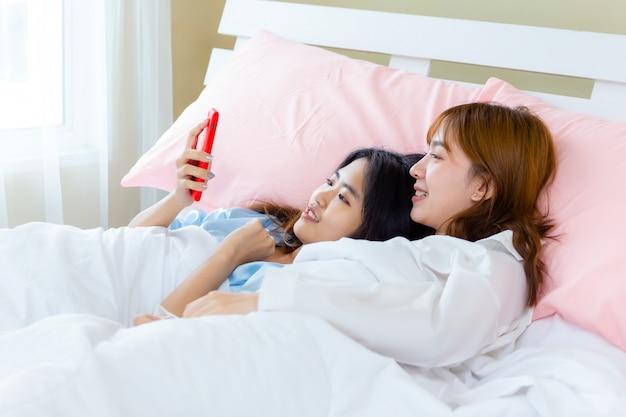 Vrolijke het gebruikssmartphone van de tienervrouw selfie op bed