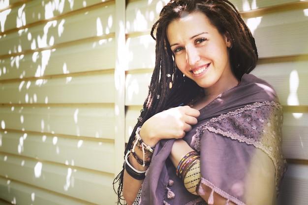 Vrolijke hippiestijl vrouw met dreadlocks portret, zonnige zomer buiten, vintage kleuren