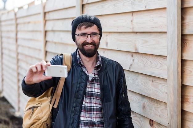 Vrolijke hipster baard man glimlachend en zelfportret met mobiele telefoon maken