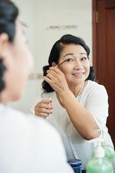 Vrolijke hogere aziatische vrouw die mascara op wimpers voor spiegel zet