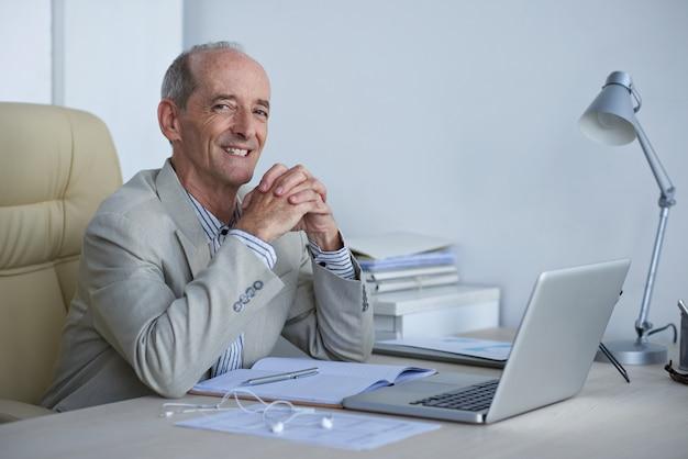 Vrolijke hogere kaukasische uitvoerende zitting bij bureau in bureau en het glimlachen voor camera
