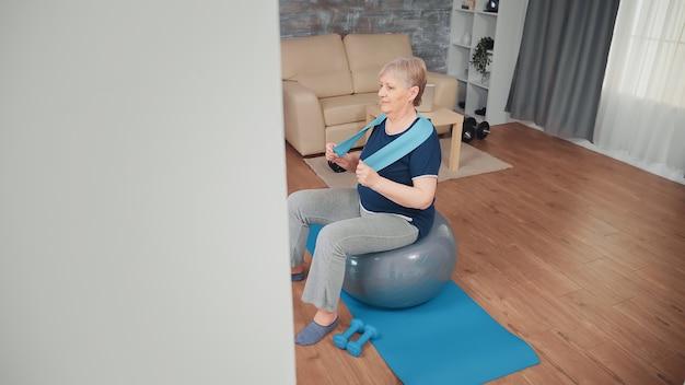 Vrolijke hogere vrouw die op saldobal uitoefent. bejaarde training thuis sport gezonde levensstijl, ouderen fitness oefening workout in appartement, activiteit en gezondheidszorg
